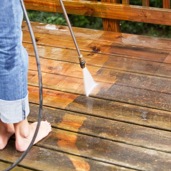 """""""A woman with rolled jean and bare feet s is using a  pressure washer sprayer to clean a weathered treated wood deck. The wood on the left has been cleaned, the right is weathered and dirty. Focus is on the wood, the nozzle is slightly soft."""""""